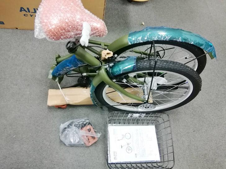 自転車はこのように分かれていて、少し自分で組み立てる必要があります。同梱品は折り畳み自転車本体の他に、サドルとハンドル、前かごとペダル、フロントライトやワイヤー錠、その他、留め具や取扱説明書が入っています。